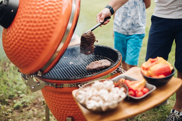 グリルで肉を調理する認識できない男。