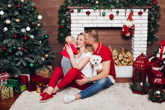 Счастливая семья сидит возле камина с маленьким сыном и милой собакой и улыбается