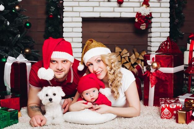 家族は幼い息子と犬と暖炉の近くの床に横たわって、カメラに笑顔