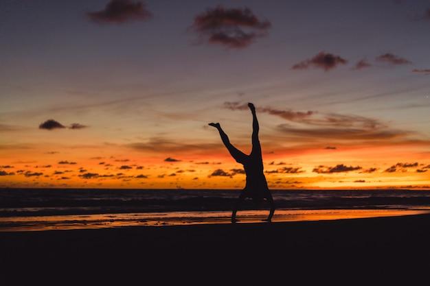 日没時に海岸の人々。人は夕日を背景にジャンプする
