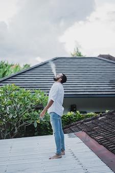 Бородатый человек, курящий на крыше