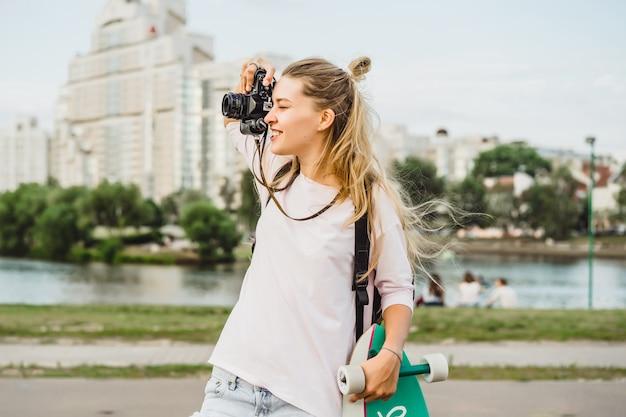 Девушка с длинными волосами с фотографией фотографировать на камеру. улица, активный спорт