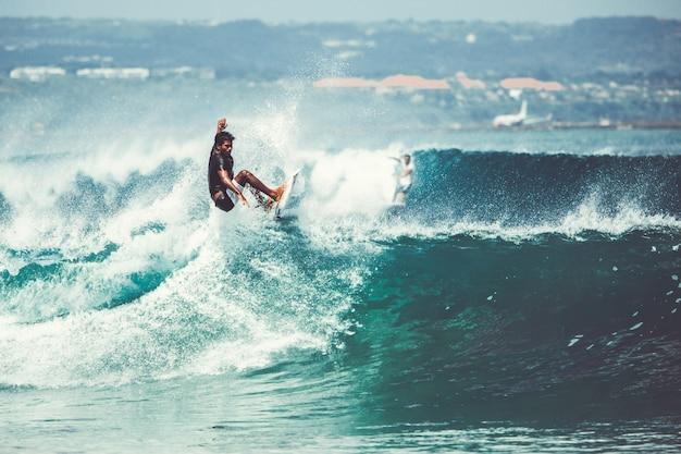 男性と女の子がサーフィンしている