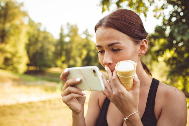 Девушка делает упражнения в парке и имеет мороженое
