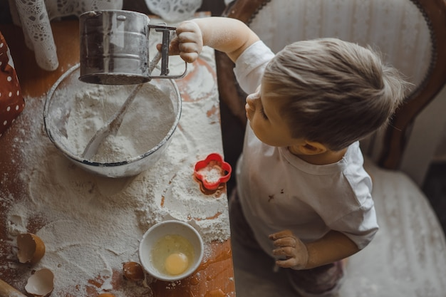 Маленький мальчик на кухне помогает маме готовить. ребенок участвует в приготовлении пищи.