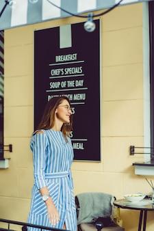 Молодая счастливая женщина в уличном кафе улыбается смеется пить кофе на террасе