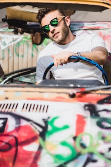 ヴィンテージカーを背景にしている若い男