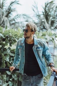 ヤシの木と緑の背景に熱帯の場所でポーズを取る若い魅力的な男