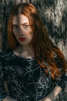 背景に自然な場所にリネンのドレスの長い赤毛の若い女性