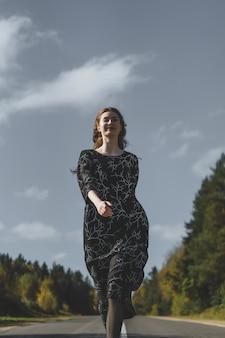 Молодая женщина с длинными рыжими волосами в льняном платье в естественном месте на заднем плане