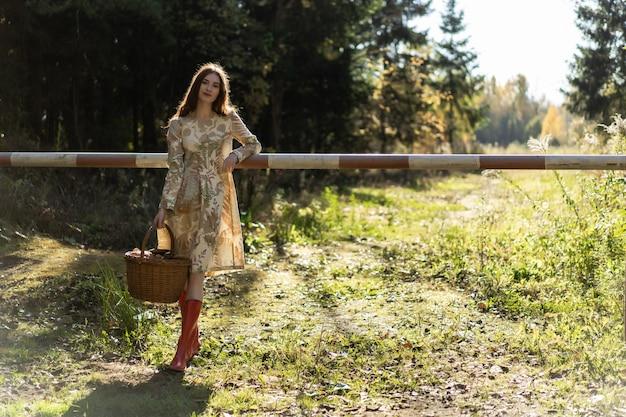 森の中でキノコを集めるリネンドレスの長い赤い髪の若い女性