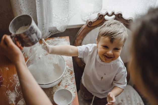 キッチンの小さな男の子は、お母さんが料理するのに役立ちます。子供は料理に関わっています。
