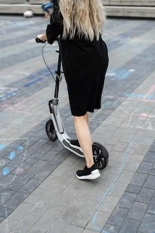 電動スクーターには長い毛を持つ若い女。電動スクーターの女の子。
