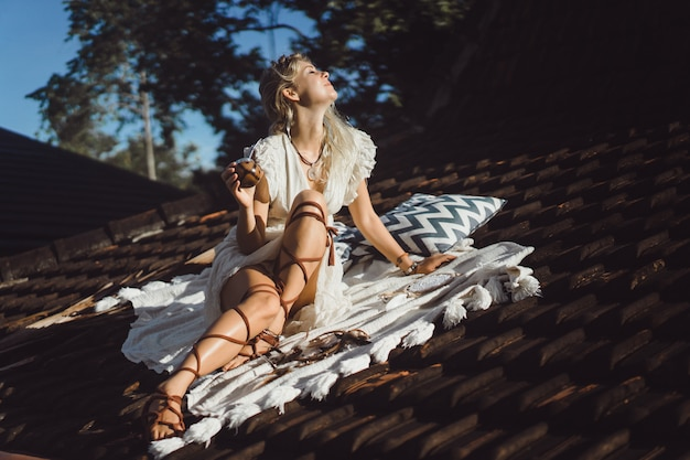 マテ茶を飲む屋根の上の長いブロンドの髪と美しいインドのヒッピーの女の子。