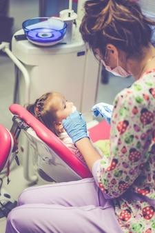 小児歯科医。歯科医の受付で小さな女の子。
