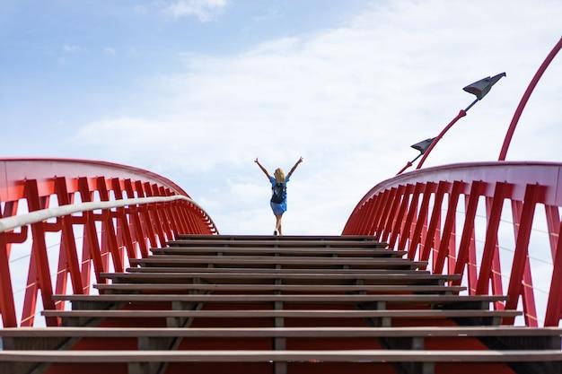 Красивая девушка в голубом платье позирует на мосту