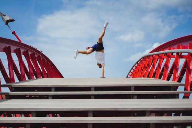 橋の上の男。逆立ち