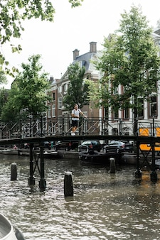 男はアムステルダムの橋の上ポーズします。