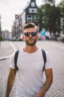 バックパックを持った男がアムステルダムの街を歩きます。