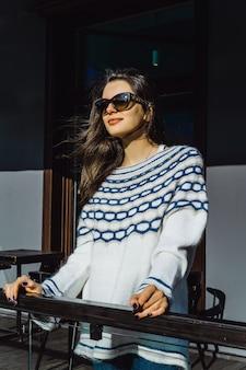 通りのカフェでサングラスの女の子