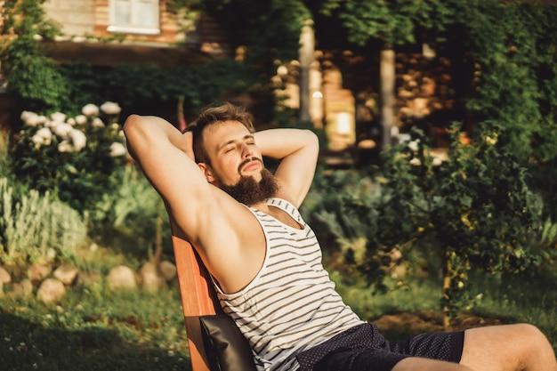 男はカントリーハウスで休んでいます。ひげのある男は緑の芝生の上で日没を楽しむ。
