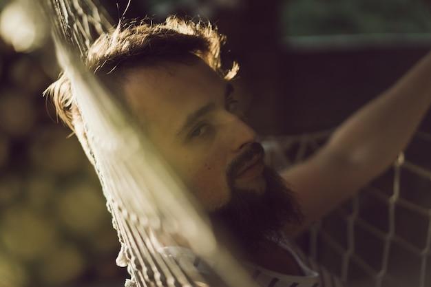 暖かい夏の日にハンモックに横たわっているひげのある男