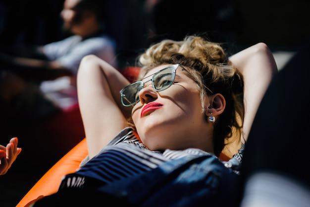 Девушка в старинных солнцезащитных очках с татуировками портрет крупным планом на улице во время пикника с друзьями. холодная девушка