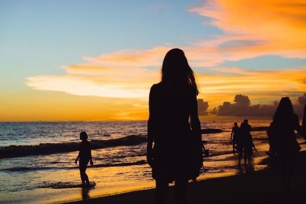 Люди на пляже на закате.