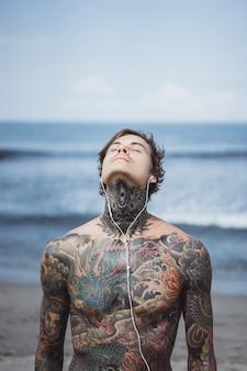 Татуированный человек с наушниками против голубого неба на берегу океана