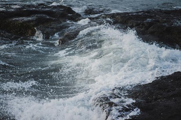 海の波が岩に砕けている。日没時に波が飛び散る。