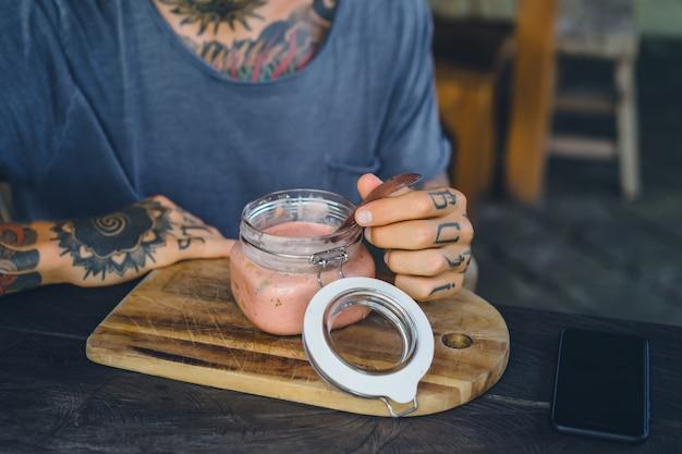 便利な朝食。美しい朝食のフィード、入れ墨の男性の手。