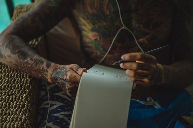 Молодой человек в татуировках в наушниках слушает музыку и рисует в блокноте.