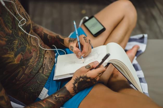 ヘッドフォンを着た入れ墨の若い男性が音楽を聴き、ノートブックに描く。