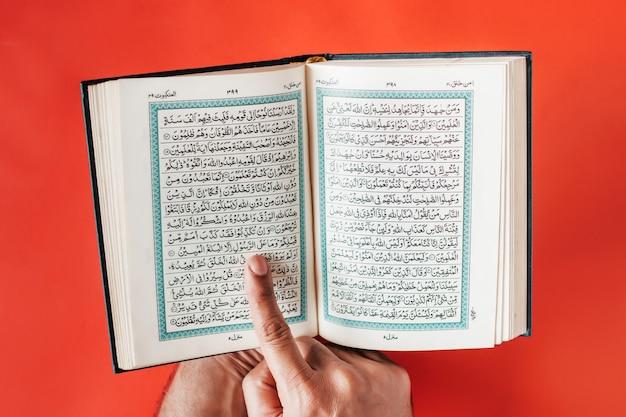 男の手が開いたコーランを握り、無地のブルゴーニュの空間を指で指します。