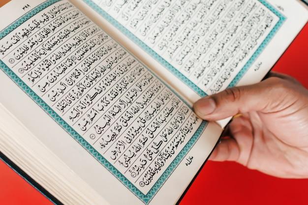 男の手が開いたコーランを無地のブルゴーニュスペースに保持しています。