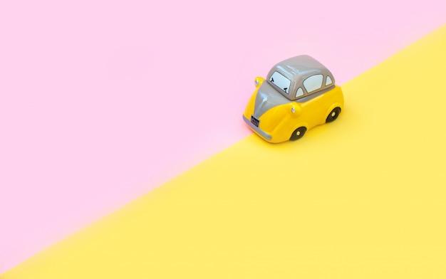 Желтый игрушечный автомобиль. изолированные на розовом и желтом фоне. концепция летних путешествий.