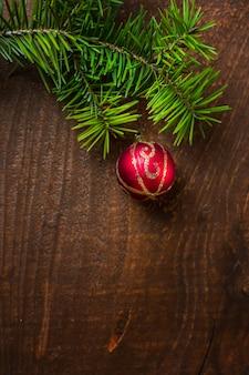 Красный елочный шар приостановлено на фоне зеленых еловых веточек старых деревянных.