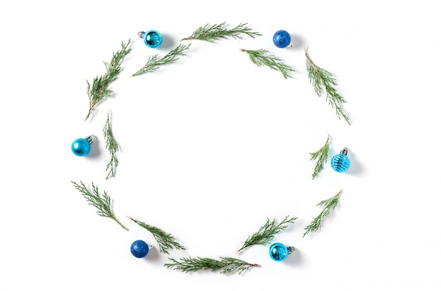 Рождественский фон синие и сиреневые шары, еловые ветки на белом фоне.