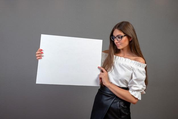 Красивая женщина, держащая пустой рекламный щит