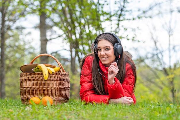 晴れた春の日に、公園の芝生の上でピクニックバスケットの隣に横たわって、音楽を聴く眼鏡の若い女性
