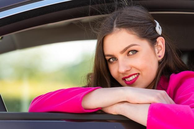 車に座って窓の外を見て若い女性