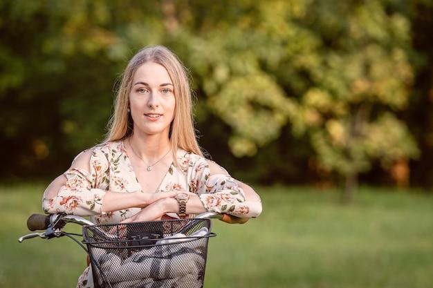 多重公園の風景に対して自転車で若い、スリム、ブロンドの女性。秋の色合い。
