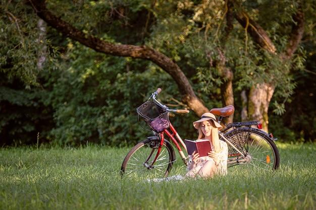 公園で若いスリムな金髪の女性が自転車の横に座って本を読んでいます。秋の色合い。