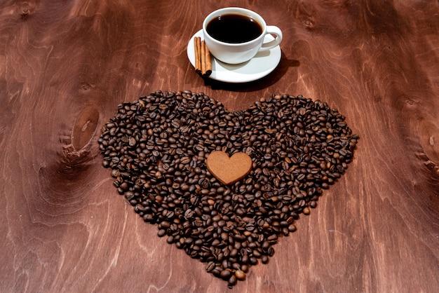 木製テクスチャボード上の白いコーヒーのマグカップ、ジンジャーブレッド、コーヒー豆の心