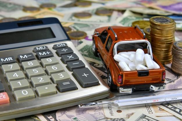 電卓、温度計、さまざまな国の通貨紙幣の貨物ボックスにタブレットを搭載したおもちゃのピックアップ。医療の可用性と医療費の増加。