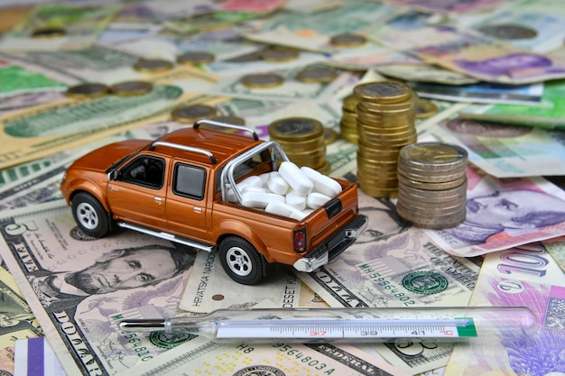 Термометр и игрушечный пикап с табличками в грузовом ящике на банкнотах разных стран. медицинская доступность и увеличение медицинских расходов.