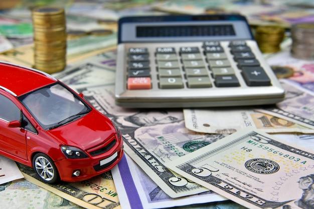 さまざまな国の通貨紙幣の電卓と赤いおもちゃの車。車の購入、レンタル、メンテナンスにかかる費用。