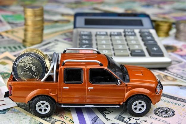 さまざまな国の通貨紙幣の貨物ボックスにコインを置いた電卓とピックアップのおもちゃの車。車の購入、レンタル、メンテナンスにかかる費用。