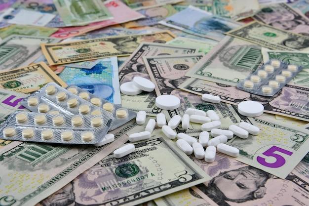 さまざまな国の通貨紙幣の丸薬。医療の可用性と医療費の増加。