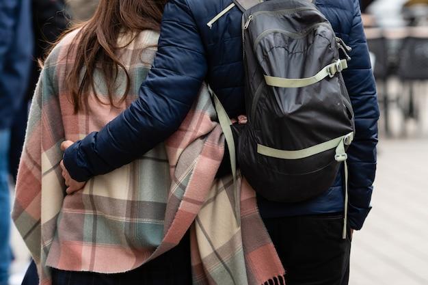 Пара обнимающихся людей идут по улице. вид сзади